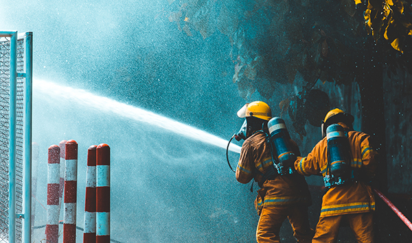 firefighters spray water to wildfire
